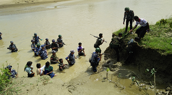 Myanmar security forces accompany Hindu villagers to the site of mass graves where their relatives were buried.