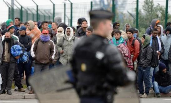 Migrants gather by a fence in Calais