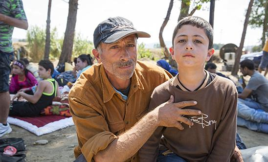 A Syrian man waits with his family of five at the Macedonia border