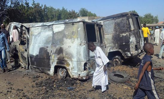 Children stand around burnt-out vehicles in Nigeria, February 2014