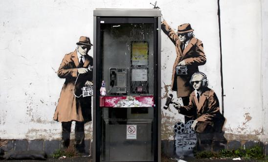 Alleged Banksy street art - spies around a telephone box in Cheltenham