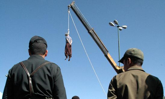 Iranian soldiers watch a man being hanged in Shiraz, south of Tehran, in 2007