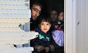 A family peeks through the window of the shipping container that is their temporary home