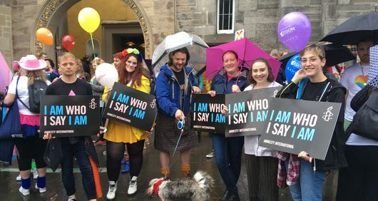 Amnesty Volunteers marching at Edinburgh Pride with trans rights placards saying 'I Am Who I Say I Am'