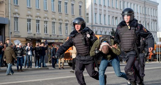 Riot police officers detain a protester during an unauthorised anti-corruption rally in central Moscow.
