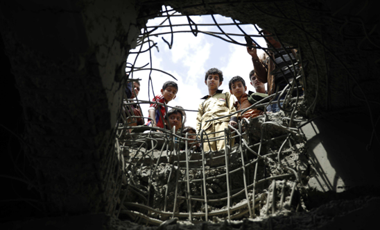 Wednesday, March 23, 2016 - boys look through a hole made by a Saudi-led airstrike on a bridge in Sanaa, Yemen © AP Photo/Hani Mohammed