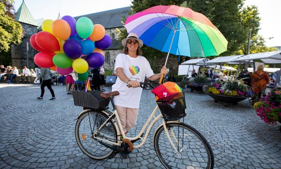 A cyclist with rainbow balloons and umbrella, at Pride.