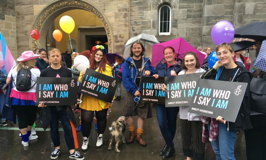 A group of six individuals from Amnesty International Scotland holding black signs with the text 'I Am Who I Say I Am' printed in pink and blue.