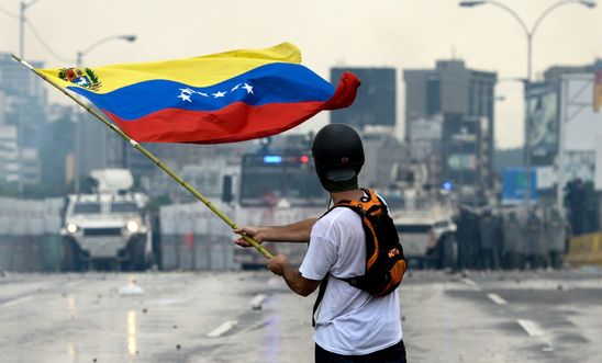 A Venezuelan opposition demonstrator waves a flag at the riot police