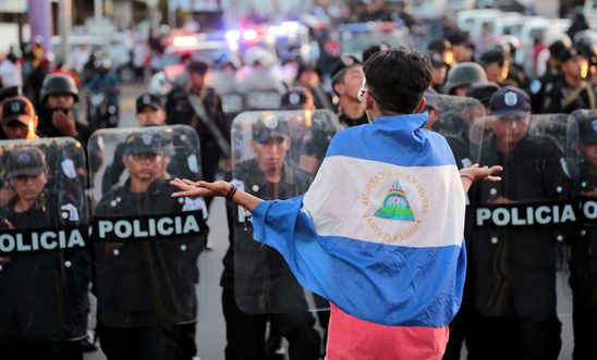 An anti-government protester wearing a national flag shouts slogans in front of a line of riot police during a protest against Nicaraguan President Ortega's government in Managua