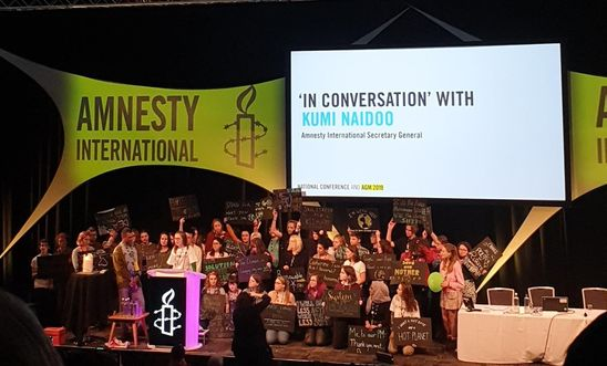 Image shows climate activists on stage at the Amnesty AGM with Kumi Naidoo