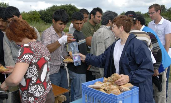 Volunteers distribute food to refugees and asylum seekers in northern France