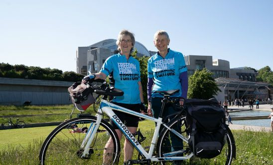 Image shows two women and a bicycle outside the Scottish Parliament