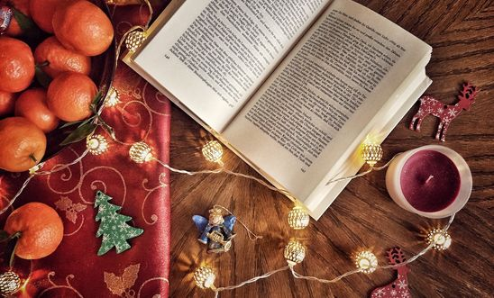 An open novel nestled next to a class of mulled wine, on a table with satsumas and gift wrapping trinkets.
