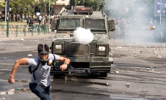 A protester runs away from security forces