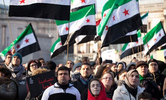 Women, men and children at a rally in London, UK carrying Syria flags