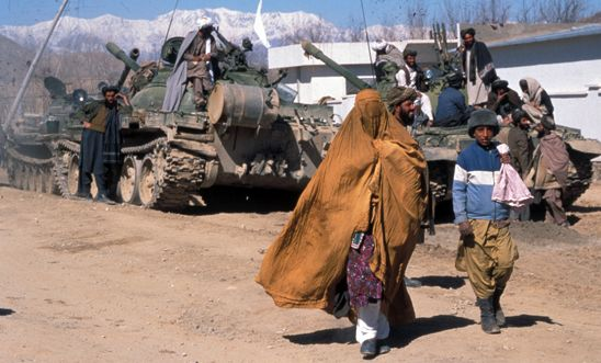 Afghan woman and boy walk by a tank in Kabul, 2004