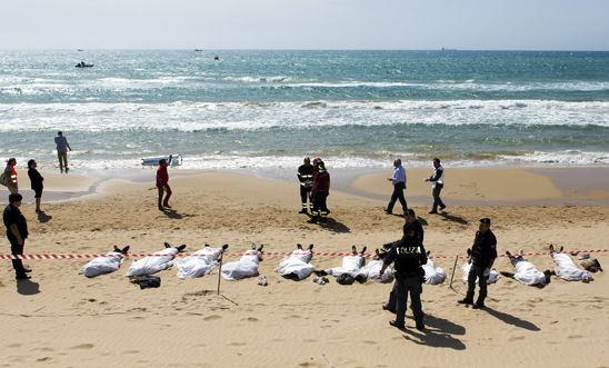 Rescue workers stand next to bodies of migrants who drowned off the coast of Sam