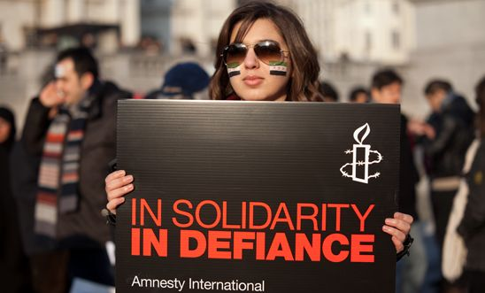 An activist holds a placard at our demonstration for solidarity with Syria, 2012