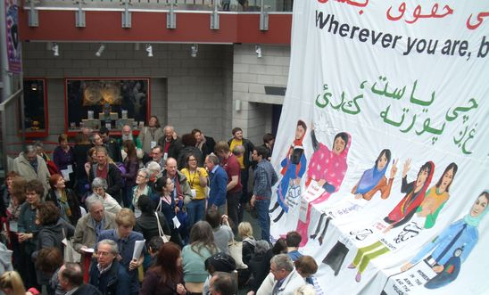 Large banner of women's rights in Afghanistan with conference delegates