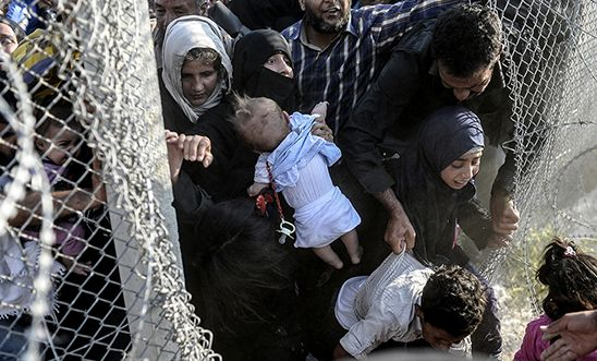 Syrians fleeing the war rush through broken down border fences to enter Turkey.