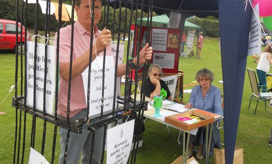 PIcture of Amnesty member in a cage, beside our stall