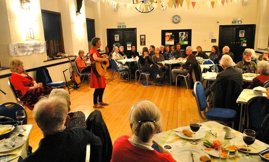 Photo of the supper concert with Saffron singing and playing her guitar