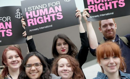 Activists hold placards saying 'I stand for human rights'