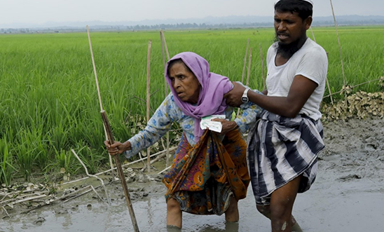 A Rohingya woman is helped to safety