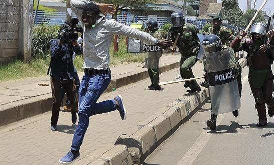 A protestor runs from anti-riot police on 26 September 2017 in Nairobi, during a demonstration to demand the removal of officials from national election oversight body