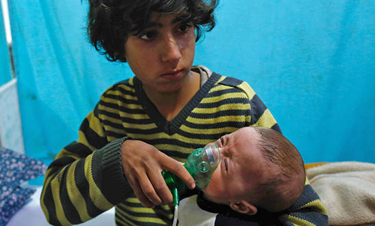 A Syrian boy holds an oxygen mask over the face of an infant at a make-shift hospital following a reported gas attack on the rebel-held besieged town of Douma in the eastern Ghouta region on the outskirts of the capital Damascus on January 22, 2018.