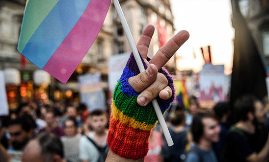 A LGBT member makes a victory sign with his fingers as he holds a rainbow flag on 21 August 2016 in Istanbul