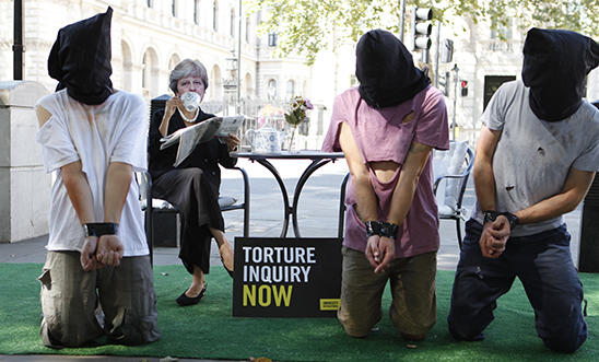 A stunt outside Downing street depicting Theresa May ignoring torture victims kneeling in front of her.
