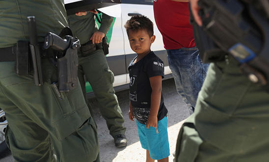 US Border Patrol agents take into custody a father and son from Honduras near the US-Mexico border, 12 June 2018