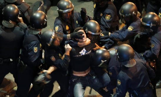 A demonstrator struggles with riot police in Madrid, 2012