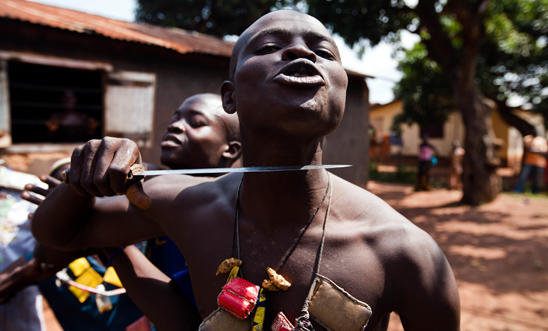 An Anti-balaka fighter holds a knife to his own throat