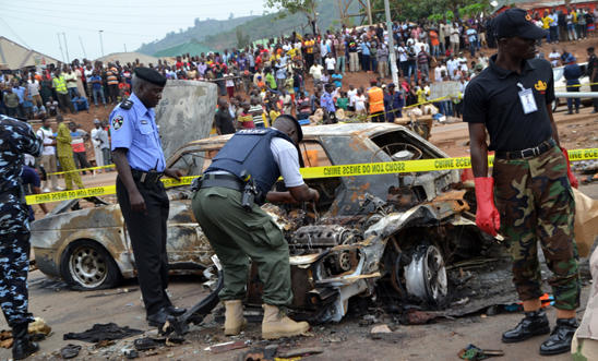 Nigerian security personnel inspect the site of a blast at Nyanya, Abuja
