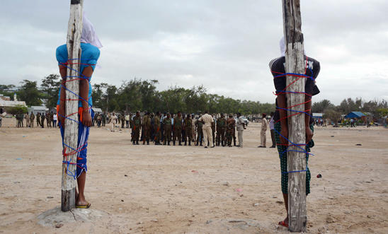 Two Somalis are tied to stakes as they await execution by firing squad