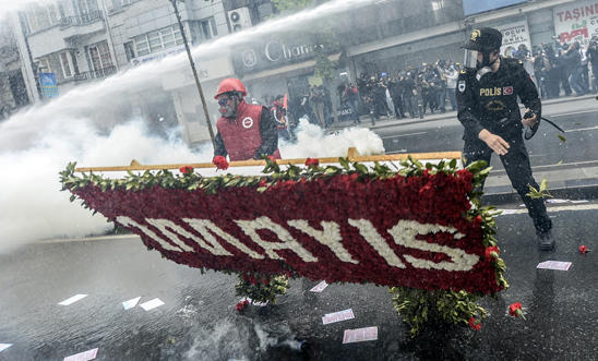 A Turkish protester is fired at with a water cannon near Taksim Square