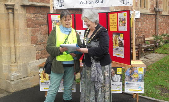 An Amnesty member with the mayor of Minehead in front of campaigning stall