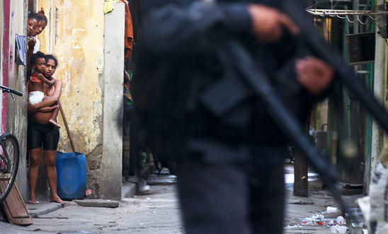 Residents look on as military police officers patrol in Complexo da Mare, favela