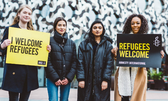 Amnesty activists stand together to welcome refugees
