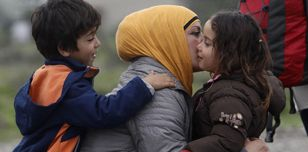 A boy and a girl hug a woman as they arrive at the transit camp for refugees near the southern Macedonian town of Gevgelija, after crossing the border from Greece, on Thursday, Oct. 8, 2015.