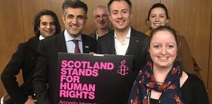 A group of people hold up an Amnesty International placard that says 'Scotland stands for human rights'