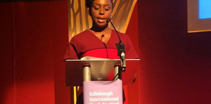 The picture shows an author standing at a podium speaking.