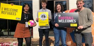 Image shows Amnesty Scotland activists with Football Welcomes banners and placards