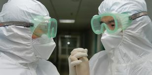 Two people in overalls, gloves and goggles, linking hands.