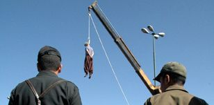 Iranian soldiers watch a man being hanged in Shiraz, Iran, in 2007