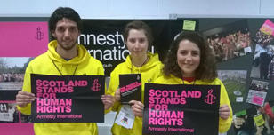 Activists holding placards reading: Scotland stands for human rights