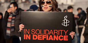 A woman holds a placard reading 'In solidarity, in defiance'